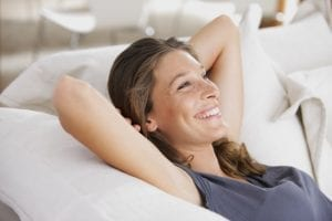 Frau lächelt auf Sofa