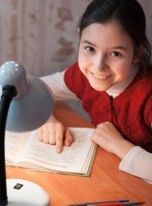 Mädchen liest am Tisch