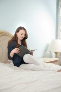 Frau liest im Bett mit Tageslichtleuchte
